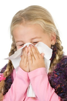 young girl with severe allergies sneezing