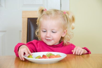 toddler enjoying a healthy fruit snack